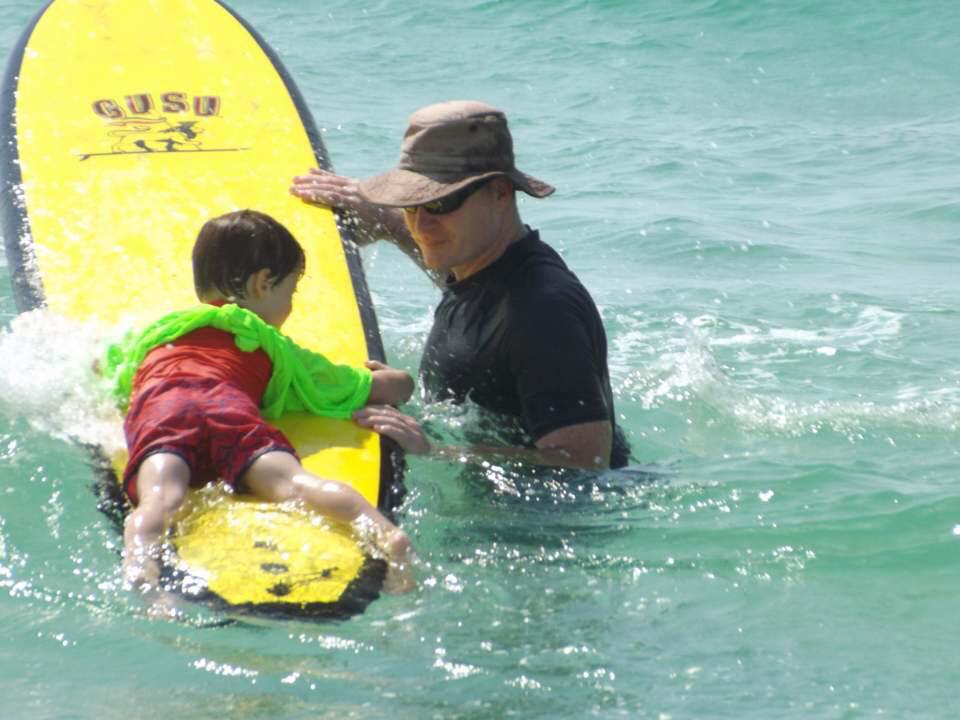 Young boy on a yellow surfboard with an adult next to him in the water