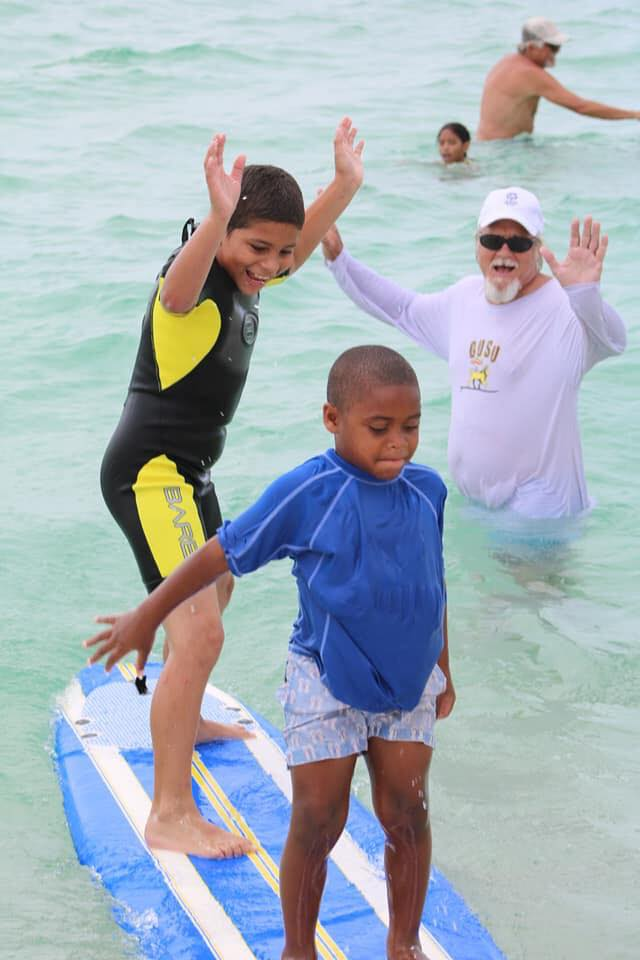 Two boys on a surfboard in the ocean