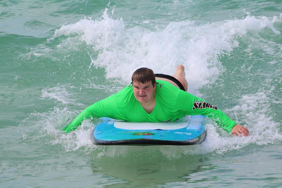 boy with green shirt laying on a surfboard riding a wave