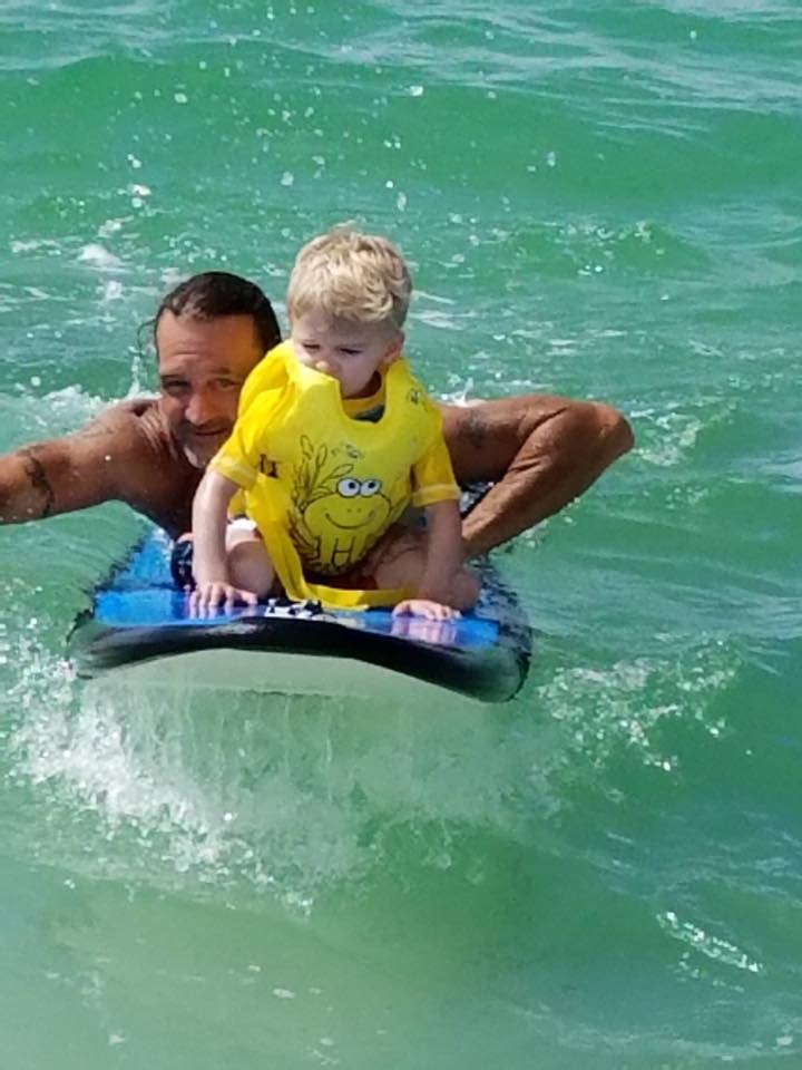 young boy and adult on a surfboard riding a wave
