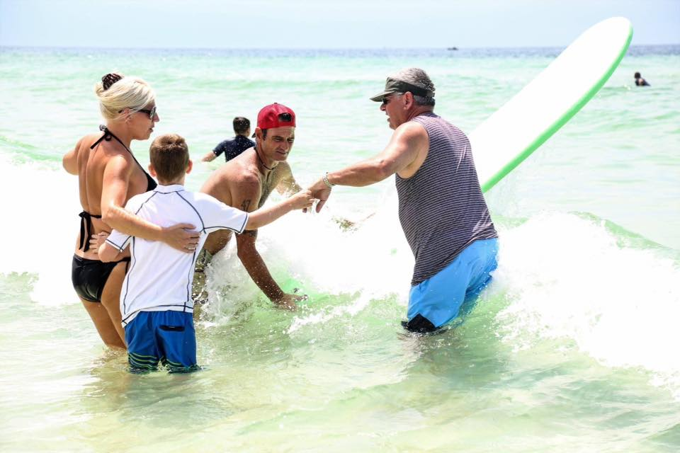 boy in white shirt being helped into the water by 3 adults