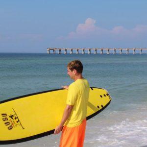 Boy holding yellow surfboard