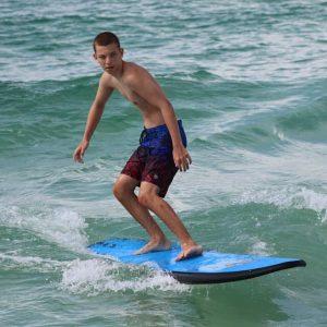 Boy surfing a blue surfboard