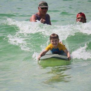 boy laying on a surfboard riding a wave