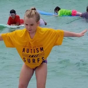 girl in yellow Autism Surfs shirt riding a wave
