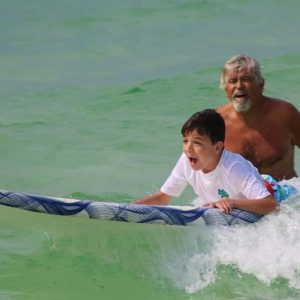 Boy in white shirt laying on surfboard with adult surf instructor helping him surf